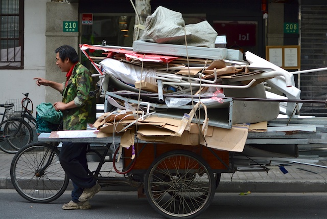 Chinese waste collector uses bicycle-pulled cart to aid his efforts in informal recycling.